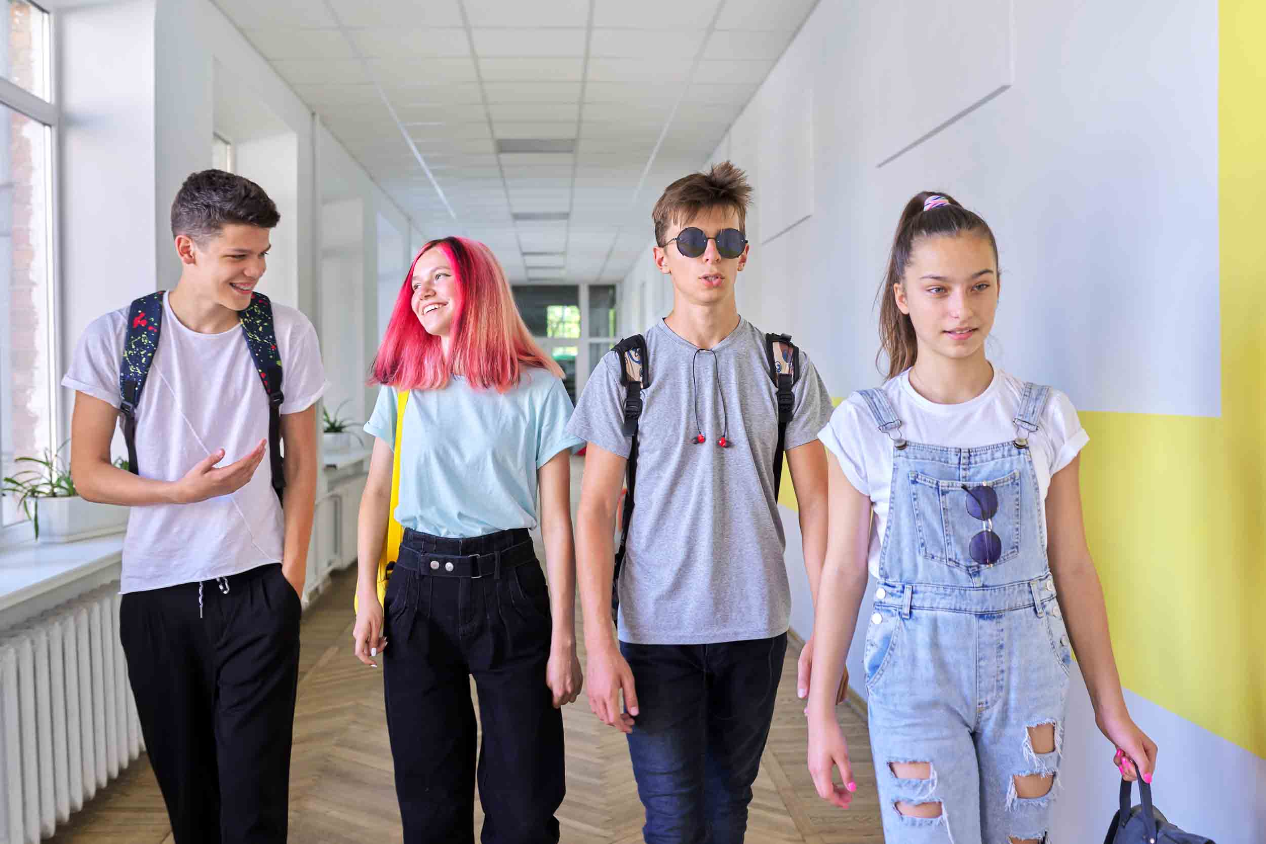 Group of teenage students walking together along school corridor, schoolchildren smiling and talking. Education, high school, adolescence concept